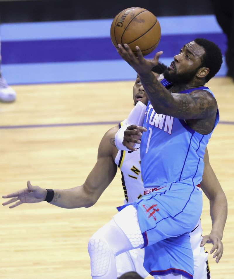 Houston Rockets' John Wall drives to the basket next to Indiana Pacers' Jeremy Lamb during the third quarter of an NBA basketball game Wednesday, April 14, 2021, in Houston. (Carmen Mandato/Pool Photo via AP)