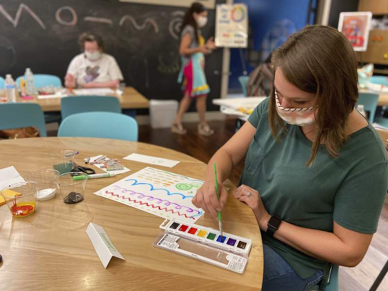 Teacher Cameron McMillan creates a painting during a visual arts workshop at the Mississippi Arts + Entertainment Experience in Meridian, Miss. on Monday, July 13, 2020. Teachers will return to school in August under new guidelines to prevent the spread of COVID-19. (Bill Graham/The Meridian Star via AP)