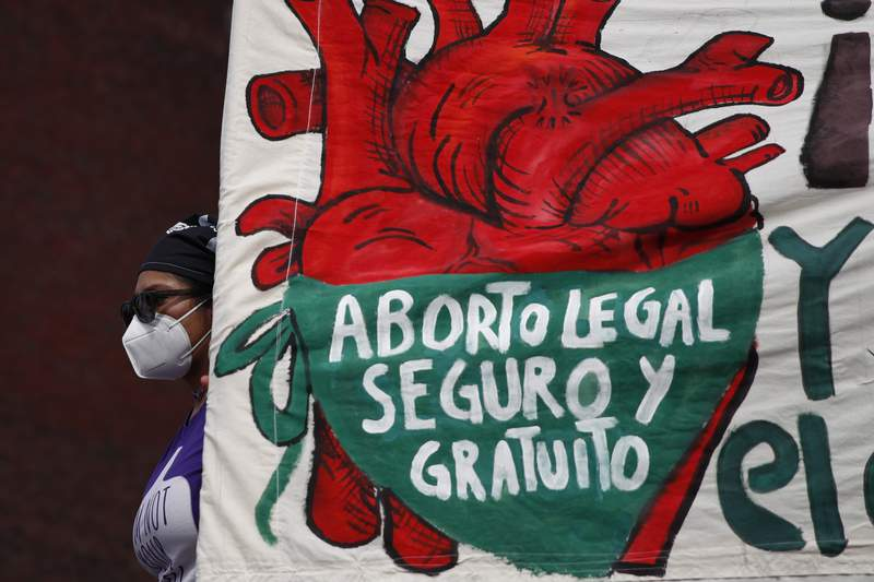 """FILE - In this Sept. 28, 2020 file photo, a woman holds a banner reading, in Spanish, """"Legal, safe, and free abortion, legalize and decriminalize abortion now, for the independence and autonomy of our bodies,"""" as abortion-rights protesters demonstrate in front of the National Congress on the """"Day for Decriminalization of Abortion in Latin America and the Caribbean,"""" in Mexico City. The Supreme Court of Mexico has on Tuesday, September 7, 2021, annulled several statutes on the northern state of Coahuila that criminalized abortion. (AP Photo/Rebecca Blackwell, File)"""