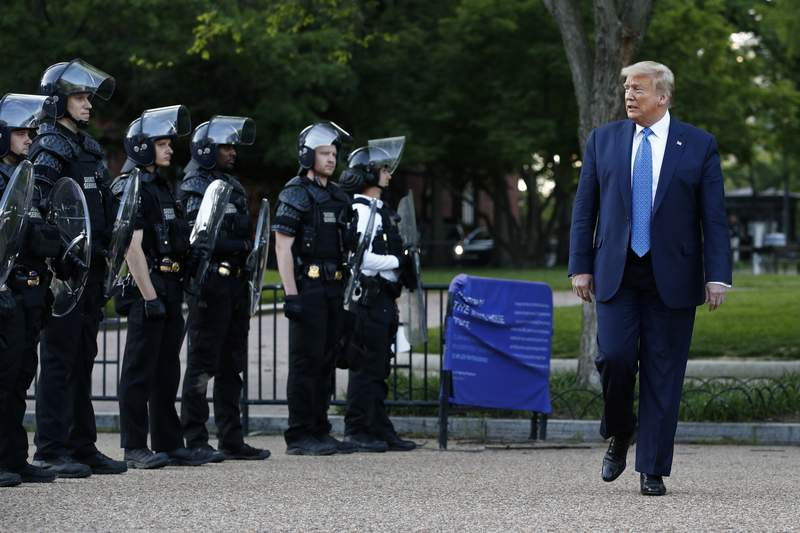 FILE - In this June 1, 2020 file photo, President Donald Trump walks past police in Lafayette Park after visiting outside St. John's Church across from the White House in Washington. An internal investigation has determined that the decision to clear racial justice protestors from an area in front of the White House last summer was not influenced by then-President Donald Trumps plans for a photo opportunity at that spot. The report released Wednesday by the Department of Interiors Inspector General concludes that the protestors were cleared by U.S. Park Police on June 1 of last year so new fencing could be installed.  (AP Photo/Patrick Semansky)