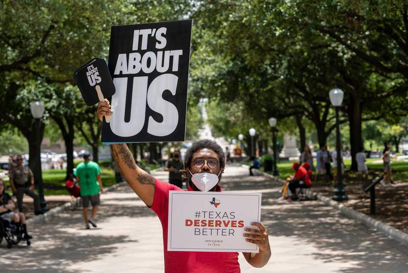 Tevin English holds signs in front of the Texas Capitol at a Voting Rights Advocacy Day rally held by various voting rights advocacy groups on July 13, 2021.