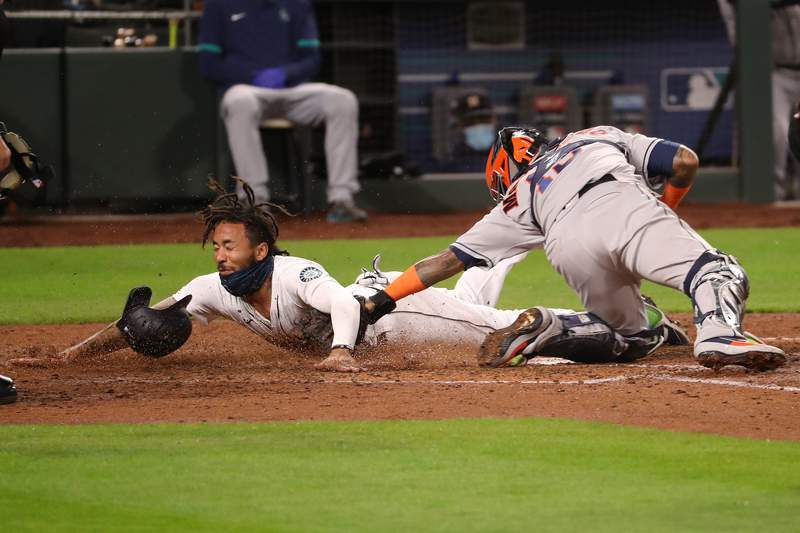 SEATTLE, WASHINGTON - SEPTEMBER 23: J.P. Crawford #3 of the Seattle Mariners beats the tag against Martin Maldonado #15 of the Houston Astros to give the Seattle Mariners a 2-0 lead in the fifth inning at T-Mobile Park on September 23, 2020 in Seattle, Washington. (Photo by Abbie Parr/Getty Images)