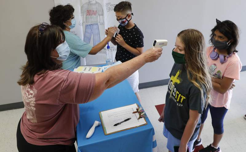 FILE - In this Tuesday, July 14, 2020 file photo, Amid concerns of the spread of COVID-19, teachers check students before a summer STEM camp at Wylie High School in Wylie, Texas. Not knowing if children are infected makes it difficult for schools to reopen safely, many experts say. Scarce data on whether infected children _ including those without symptoms _ easily spread the disease to others complicates the issue, said Jeffrey Shaman, a Columbia University infectious disease specialist. (AP Photo/LM Otero)