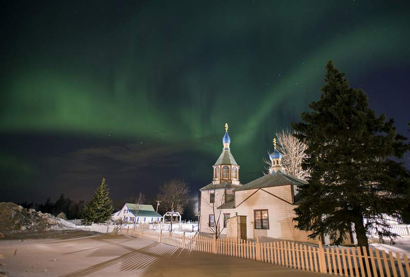 FILE - In this March 17, 2013, file photo, the aurora borealis, or northern lights, fill the night sky above the Holy Assumption of the Virgin Mary Russian Orthodox church in Kenai, Alaska. The phenomenon occurs when electrically charged particles from the sun enter the earth's atmosphere. Robert Rutledge, of the U.S. government's space weather prediction center said Thursday, Dec. 10, 2020, that stargazers in the continental 48 states have very little chance of seeing the northern lights this week despite an initial promising forecast. (AP Photo/M. Scott Moon, File)
