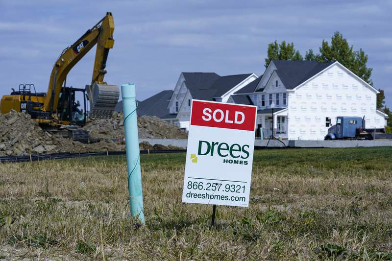"""A """"sold"""" sign sits on a lot as new home construction continues in Westfield, Ind., Friday, Sept. 25, 2020.  U.S. long-term mortgage rates were little changed this week of Oct. 29, after marking a new all-time low last week. Home loan rates have declined through the year amid economic anxiety in the recession set off by the coronavirus pandemic.  (AP Photo/Michael Conroy)"""