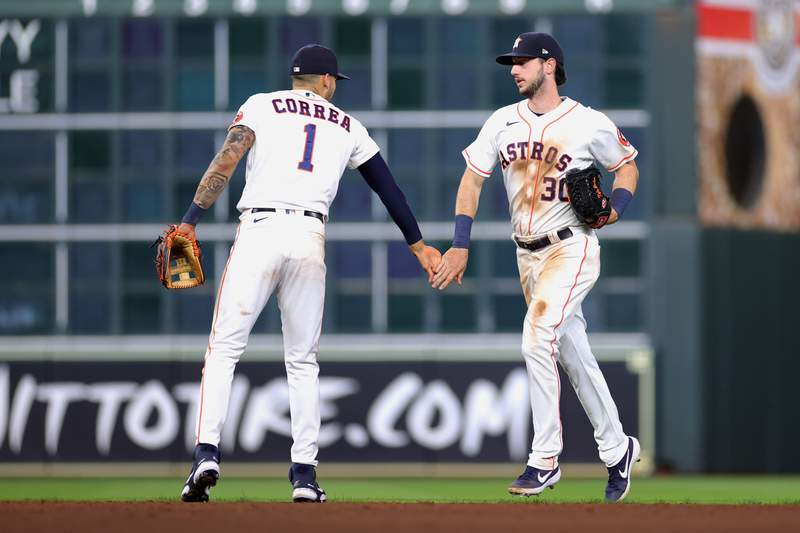 HOUSTON, TEXAS - APRIL 22: Carlos Correa #1 of the Houston Astros high fives Kyle Tucker #30 following a win over the Los Angeles Angels 8-2 at Minute Maid Park on April 22, 2021 in Houston, Texas. (Photo by Carmen Mandato/Getty Images)