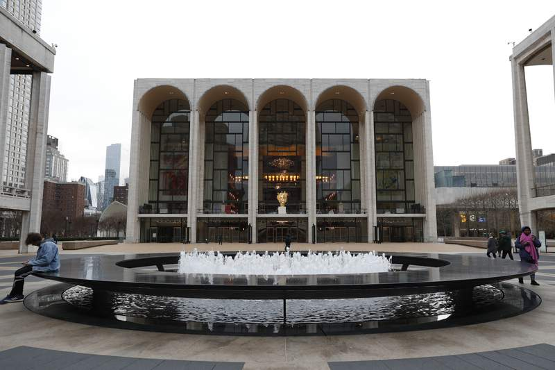 FILE - This March 12, 2020, file photo shows Josie Robertson Plaza in front of The Metropolitan Opera house, background center, at Lincoln Center in New York. The Metropolitan Opera reached a four-year agreement with the union for its orchestra, the last major deal needed for the company to resume performances following a 1 1/2-year layoff caused by the coronavirus pandemic. (AP Photo/Kathy Willens, File)