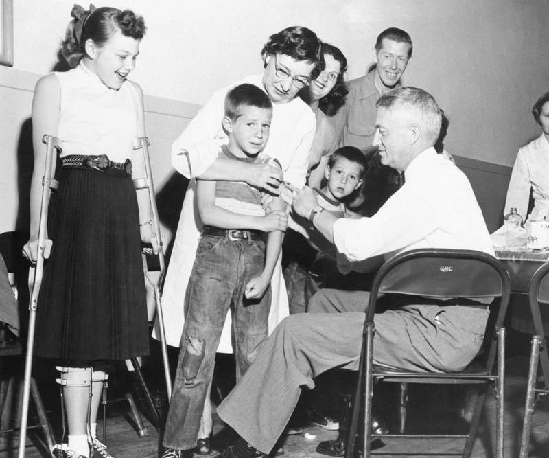 4/16/1955 -- Dr. William S. Burgoyne gives a shot of the Salk anti-polio vaccine to Michael Urnezis, 6, while the boy's sister, Joanne, 12, a polio victim, looks on April 16.