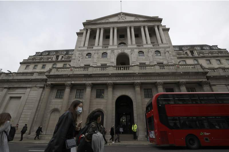 FILE - In this Wednesday, March 11, 2020 file photo, pedestrians wearing face masks walk past the Bank of England in London. The Bank of England kept its main interest rate at the record low of 0.1% but warned that inflation is set to be double its target rate by the end of his year largely as a result of a sharp spike in energy prices. The decision Thursday, Sept. 23, 2021 from the central banks nine-member Monetary Policy Committee was unanimous, though two members voted to start reining in the banks stimulus program, which has aimed to keep borrowing rates low in financial markets.  (AP Photo/Matt Dunham, File)