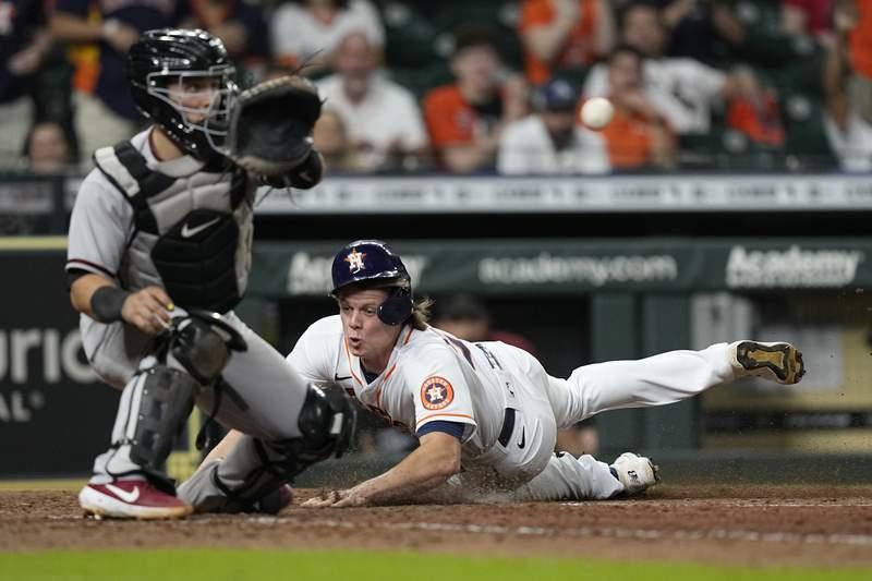 Houston Astros' Jake Meyers, right, scores as Arizona Diamondbacks catcher Daulton Varsho reaches for the ball during the 10th inning of a baseball game Saturday, Sept. 18, 2021, in Houston. (AP Photo/David J. Phillip)