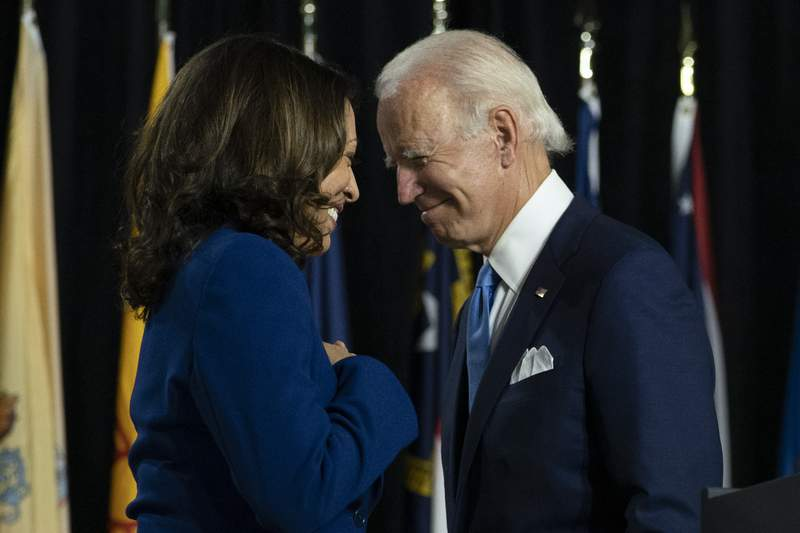 FILE - In this Aug. 12, 2020, file photo, Democratic presidential candidate former Vice President Joe Biden and his running mate Sen. Kamala Harris, D-Calif., pass each other as Harris moves to the podium to speak during a campaign event at Alexis Dupont High School in Wilmington, Del. (AP Photo/Carolyn Kaster, File)