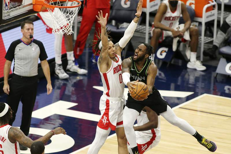 Minnesota Timberwolves guard Jaylen Nowell (4) shoots against Houston Rockets forward Sterling Brown (0) in the fourth quarter during an NBA basketball game, Friday, March 26, 2021, in Minneapolis. (AP Photo/Andy Clayton-King)