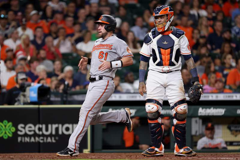 HOUSTON, TEXAS - JUNE 29: Austin Wynns #61 of the Baltimore Orioles crosses the plate ahead of Martin Maldonado #15 of the Houston Astros during the fifth inning at Minute Maid Park on June 29, 2021 in Houston, Texas. (Photo by Carmen Mandato/Getty Images)