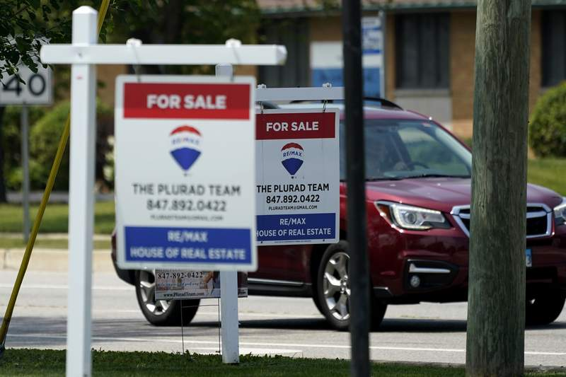 """""""For Sale"""" signs are seen outside a home in Glenview, Ill., Tuesday, July 27, 2021.  Mortgage rates were flat to lower last week, Aug. 5, with the average for the key 30-year home loan below 3% for the sixth straight week.    (AP Photo/Nam Y. Huh)"""