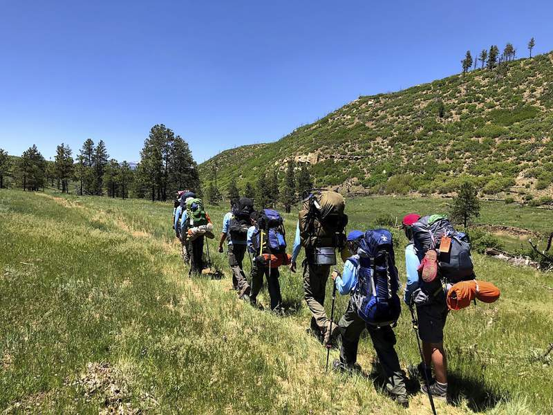 In this June 10, 2021 photo provided by Barry Bedlan, members of Troop 298 of Frisco, Texas are among the first to embark a 12-day trek across the Philmont Scout Ranch, outside Cimarron, N.M. Boy Scout and Girl Scouts leadership say their summer camps are full, special events are sold out, and theyre expecting many thousands of families  some new to scouting, some who left during the pandemic  to sign up now that activities are occurring in-person rather than virtually. (Barry Bedlan via AP)