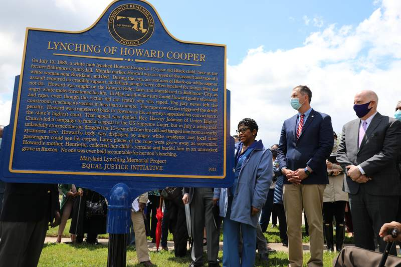 Maryland Gov. Larry Hogan, far right, Baltimore County Executive John Olszewski and Maryland House Speaker Adrienne Jones stand next to a new historic marker on Saturday, May 8, 2021 in Towson, Md., that memorializes Howard Cooper, a 15-year-old who was dragged from a jailhouse and hanged from a tree by a mob of white men in 1885. Hogan signed a posthumous pardon for 34 men, including Cooper, who were lynched in the state between 1854 and 1933 without due process against allegations they faced. (AP Photo/Brian Witte)
