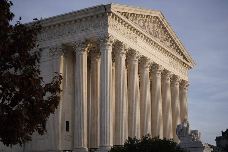 In this Nov. 5, 2020 file photo, The Supreme Court is seen in Washington.  The Supreme Court has dismissed as premature a challenge to President Donald Trump's plan to exclude people living in the country illegally from the population count used to allot states seats in the House of Representatives. But the courts decision Friday is not a final ruling on the matter and it's not clear whether Trump will receive final numbers from the Census Bureau before he leaves office next month. (AP Photo/J. Scott Applewhite)