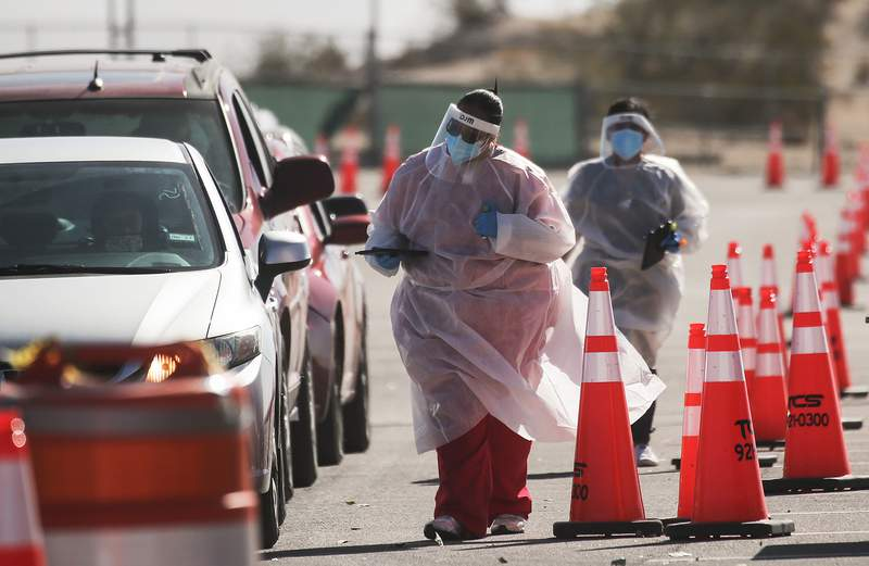 EL PASO, TEXAS - NOVEMBER 14: Frontline healthcare workers greet incoming vehicles at a drive-in COVID-19 testing site amid a surge of COVID-19 cases on November 14, 2020 in El Paso, Texas. (Photo by Mario Tama/Getty Images)