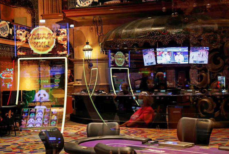 A woman is seen reflected wearing a protective face mask, amid the coronavirus disease outbreak, outside a closed poker room in a casino in New Orleans on Aug. 30, 2020. (Credit: REUTERS/Shannon Stapleton)