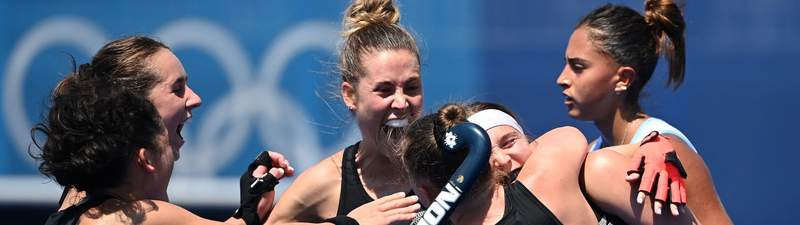 New Zealand's Holly Pearson (27) celebrates with teammates after scoring against Argentina as Argentina's Valentina Raposo Ruiz De Los Llanos reacts behind them, during their women's pool B match of the Tokyo 2020 Olympic Games field hockey competition, at the Oi Hockey Stadium in Tokyo on July 25, 2021.