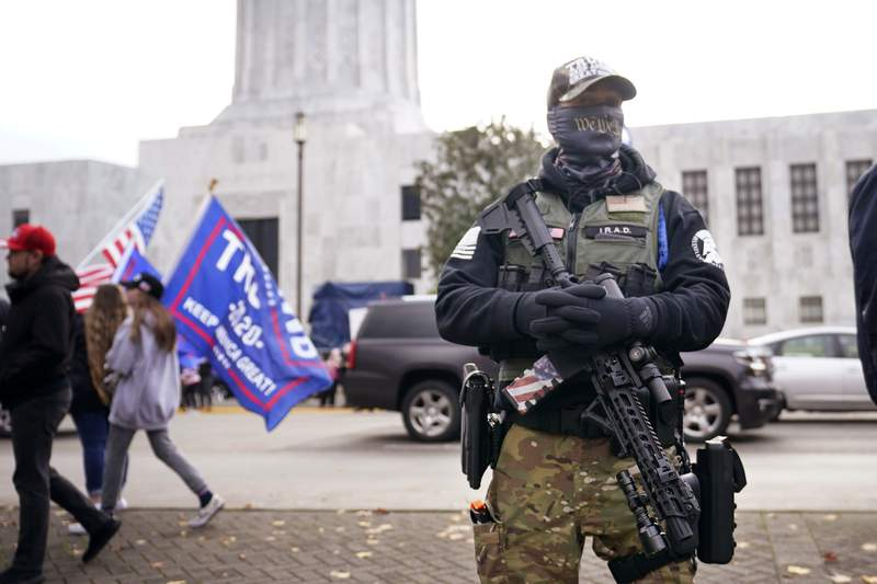 FILE - In this Nov. 7, 2020, file photo, a man holds a gun as he stands in front of the Oregon State Capitol building in Salem, Ore. Gov. Kate Brown on Tuesday, June 1, 2021, signed a bill that bans guns from the Oregon Capitol, changing a law that allowed concealed handgun licensees to bring firearms into the building. (AP Photo/Marcio Jose Sanchez, File)