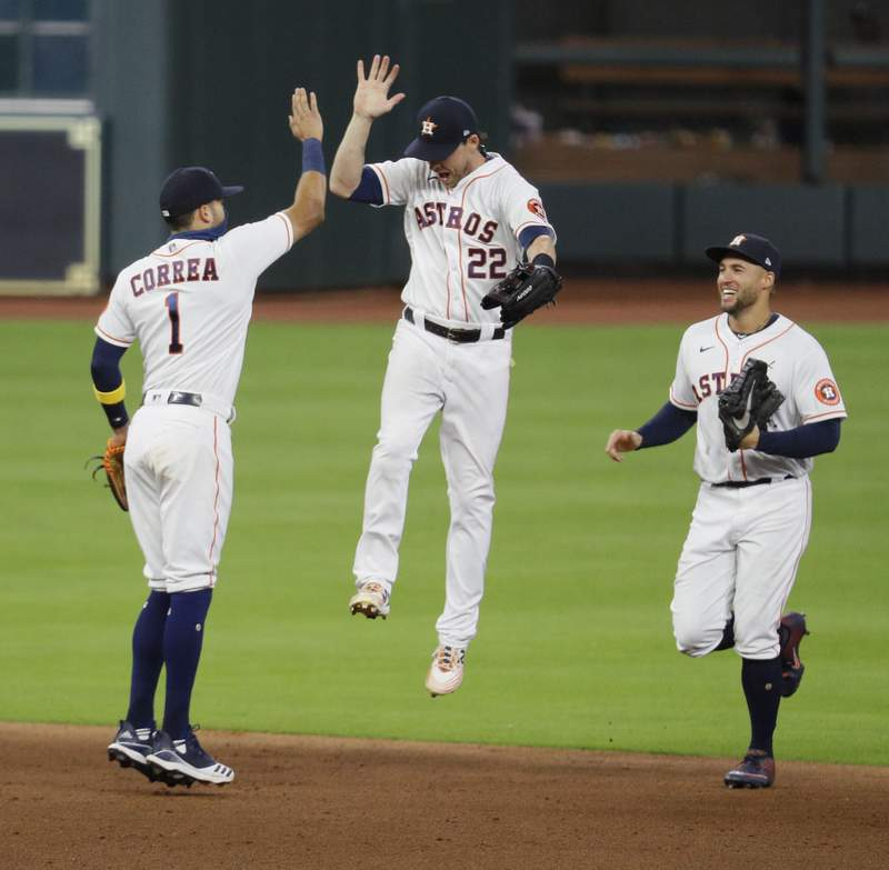 HOUSTON, TEXAS - SEPTEMBER 17: Carlos Correa #1 of the Houston Astros high fives Josh Reddick #22 as George Springer #4 looks on after a 2-1 win over the Texas Rangers at Minute Maid Park on September 17, 2020 in Houston, Texas. (Photo by Bob Levey/Getty Images)