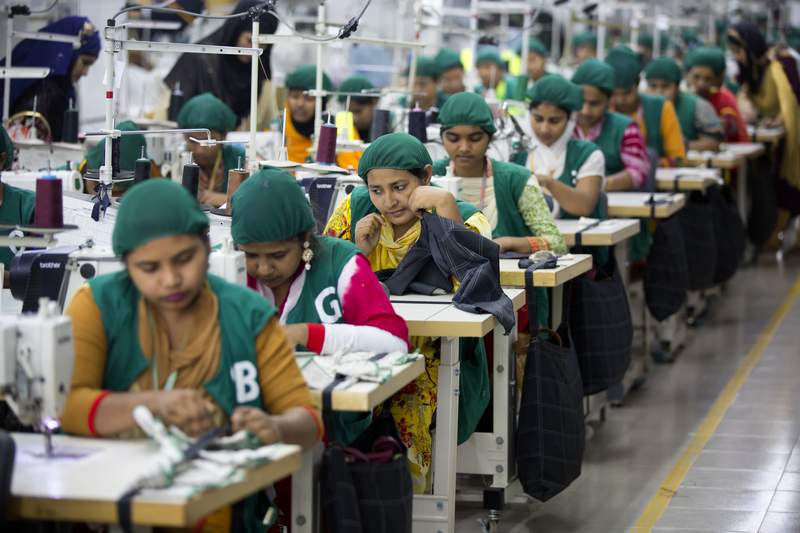 FILE - In this April 19, 2018 file photo, trainees work at Snowtex garment factory in Dhamrai, near Dhaka, Bangladesh. Bangladesh is gradually reopening its hundreds of garment factories after nearly one month of closure following a government decision for a nationwide lockdown amid concern that coronavirus could spread widely among the industrys millions of workers, an industry leader said Tuesday.  (AP Photo/A.M. Ahad, File)