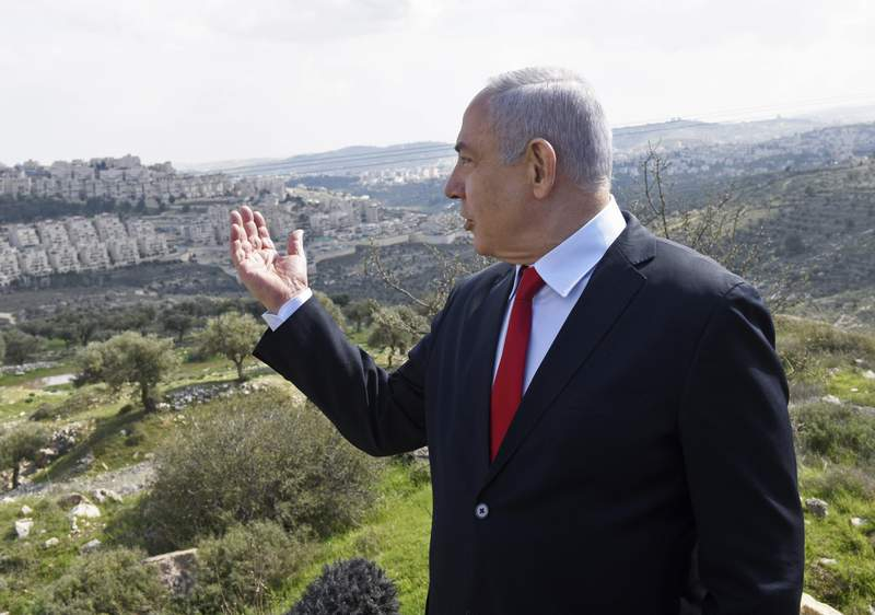FILE - In this Feb. 20, 2020 file photo, Israeli Prime Minister Benjamin Netanyahu visits the area where a new neighborhood is to be built in the East Jerusalem settlement of Har Homa. A senior Emirati official warned Wednesday, June 17, 2020 that Israel's planned annexation of parts of the West Bank could lead Arab states to call for a single binational state for Israelis and Palestinians. (Debbie Hill/Pool Photo via AP, File)