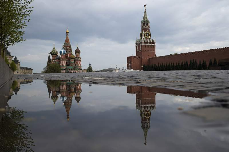 FILE - This Thursday, May 7, 2020 file photo shows the Kremlin's Spasskaya Tower, center, and St. Basil's Cathedral, left, reflected in rain water puddles in the empty Red Square during the evening rush hour in Moscow, Russia. A Kremlin-linked social media disinformation operation, dubbed Secondary Infektion by researchers, that sought to interfere with the 2016 U.S. election has continued its work to divide and discredit Western democracies, a new report finds  but its effectiveness has been limited by its own cautious tactics. While the groups work has slowed, it was operational as of 2020. (AP Photo/Pavel Golovkin)