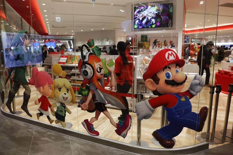 FILE - In this Jan. 23, 2020, file photo, Nintendo characters, including Mario, right, are seen on a glass of its official store in Tokyo. Nintendos April-June profit declined 13% from the same period the previous year, when the hit game Animal Crossing: New Horizons had dramatically boosted sales. (AP Photo/Jae C. Hong, File)