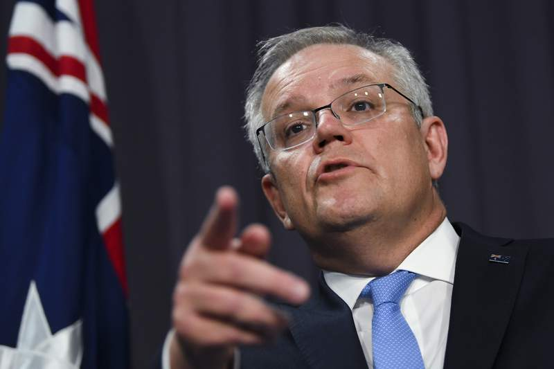 Australian Prime Minister Scott Morrison speaks to the media during a press conference at Parliament House in Canberra, Thursday, Nov. 12, 2020. Morrison said he telephoned U.S. President-elect Joe Biden and invited him to Down Under next year to celebrate the 70th anniversary of their shared defense treaty. (Lukas Coch/AAP Image via AP)