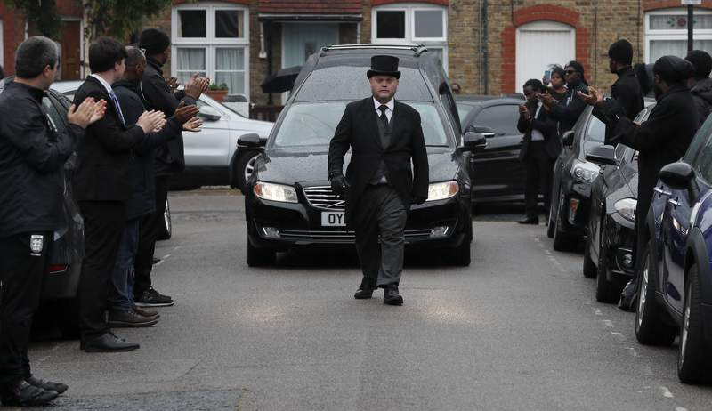 In this photo taken on Thursday, June 11, 2020, grass roots soccer referees form a guard of honour and clap as the hearse carrying the coffin of  Jermaine Wright, a pharmacist and a referee of the Hackney Marshes grassroots football league, passes by, on the day of his funeral, in London. Wright, affectionately known as Mr. Hackney Marshes, served as both an on-field referee and a behind-the-scenes catalyst in the Hackney & Leyton Sunday Football League   as vice chairman, schedule secretary, results secretary, press officer, and head official  before he died on April 27, 2020 from COVID-19. (AP Photo/Frank Augstein)