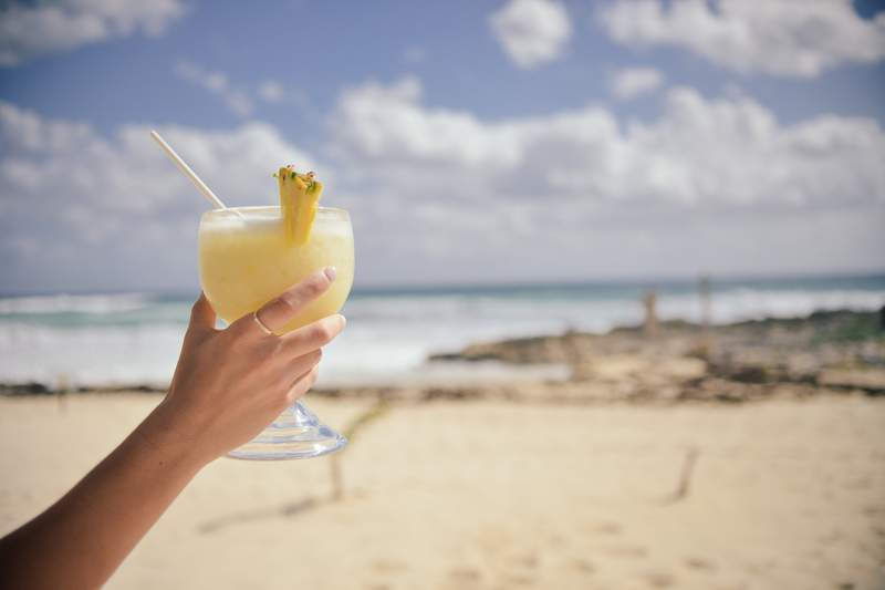 Beach goer holding glass of piña colada