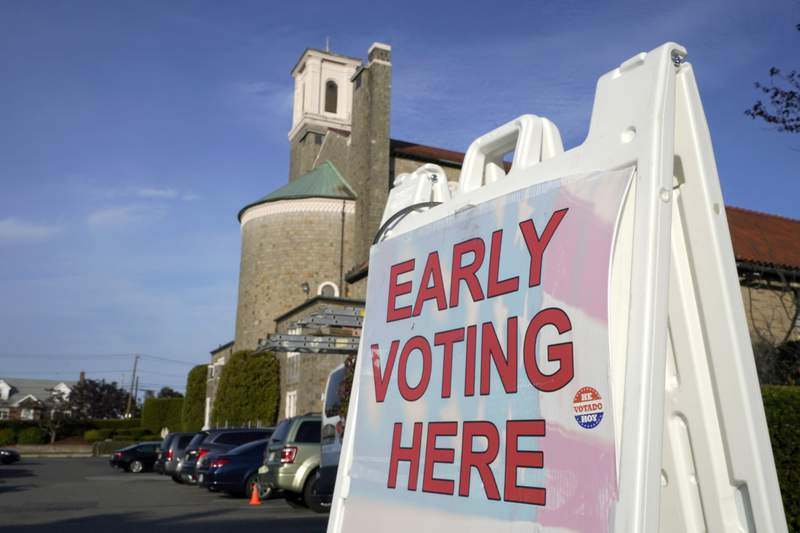 A sign stands outside Saint Anthony of Padua Church, in Revere, Mass., Monday, Oct. 19, 2020, during early in-person voting at a multiple precinct polling station in the basement of the church. (AP Photo/Steven Senne)
