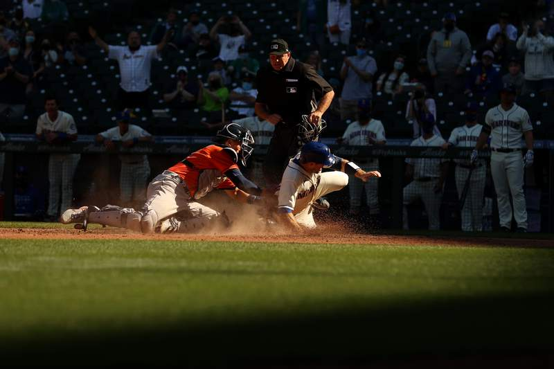 Tom Murphy #2 of the Seattle Mariners beats the tag by Jason Castro #18 of the Houston Astros to score off an RBI double by Mitch Haniger #17 during the seventh inning at T-Mobile Park on April 18, 2021 in Seattle, Washington.