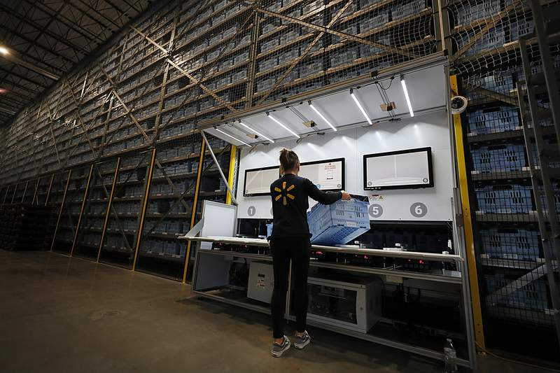 SALEM, MA - JANUARY 8: A Walmart employee loads up the Alphabot with an empty cart to be filled with a customer's online order at a Walmart micro-fulfillment center in Salem, MA on Jan. 8, 2020. Walmart has teamed up with Alert Innovation, a robotics engineering team firm in North Billerica, to build the 20,000-square-foot, semi-automated miniature warehouse next to a Walmart Superstore. Humans and robots work together to quickly pack thousands of grocery items that were ordered online from massive shelves. Each robot has geared wheels that let it climb up or down through horizontal shafts. When it reaches the right level, the robot rolls up to the correct bin, plucks it from the shelf, then descends to a packing station. The robot passes the bin to a Walmart worker who picks out the correct item and plops it into a different bin lined with standard grocery bags. (Photo by Suzanne Kreiter/The Boston Globe via Getty Images)