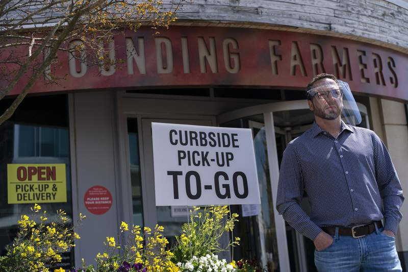 In this April 15, 2020, photo, Dan Simons, one of the owners of Founding Farmers, stands outside his restaurant in Potomac, Md. Founding Farmers is closed to in-restaurant dining during the coronavirus outbreak but they are providing delivery, and curbside pick-up to-go, for meals and groceries. (AP Photo/Carolyn Kaster)