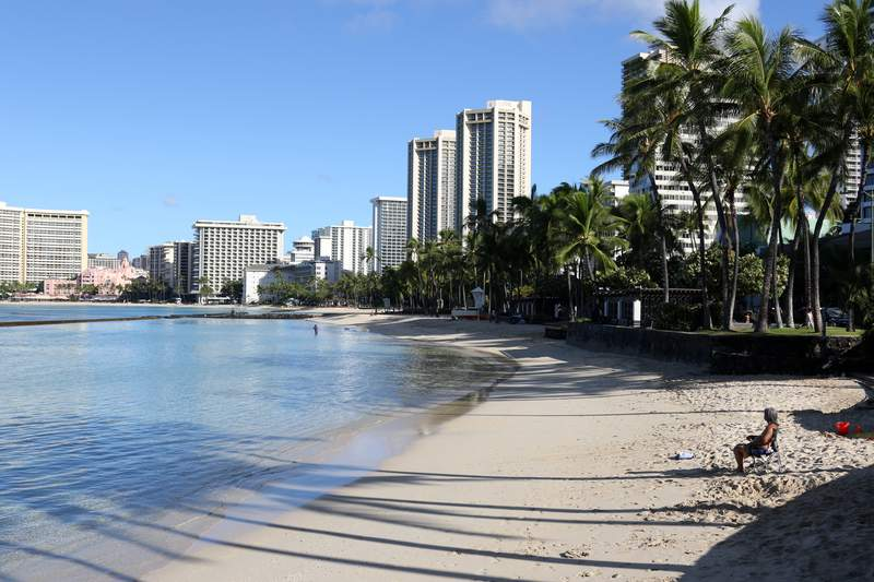 FILE - A man sits on a nearly empty Waikiki Beach in Honolulu, Friday, Oct. 2, 2020. Tourists are traveling to Hawaii in larger numbers than officials anticipated, and many are wandering around Waikiki without masks, despite a statewide mandate to wear them in public. (AP Photo/Caleb Jones, file)