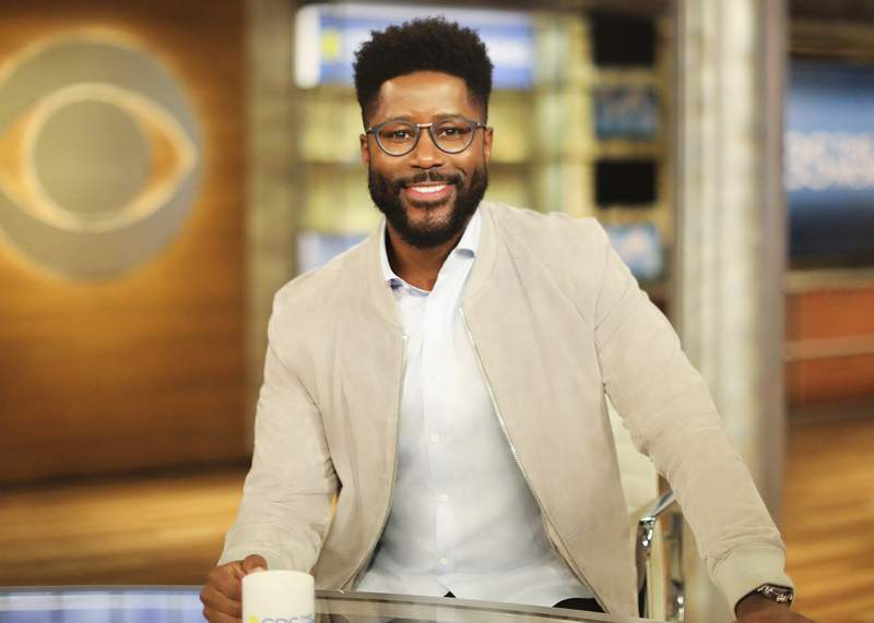 """This image provided by CBS shows Nate Burleson on the set of """"CBS This Morning."""" The former NFL player will join Gayle King and Tony Dokoupil on the show. (Michele Crowe/CBS via AP)"""