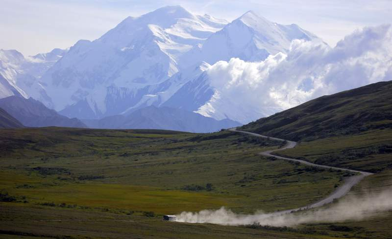 FILE - A tour bus kicks up dust during a sunny day at Denali National Park in Alaska as Mount Denali appears in the background on Thursday, Aug. 8, 2013. Road access in the popular national park in Interior Alaska is being restricted due to a long-running landslide issue that has been exacerbated by climate change, the park announced Tuesday, Aug. 24, 2021. (AP Photo/Manuel Valdes, File)