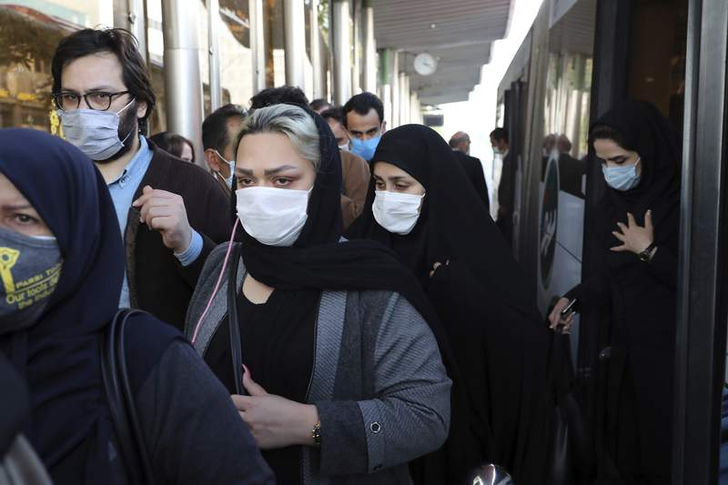 FILE - In this Sunday, Oct. 11, 2020 file photo, people wear protective face masks to help prevent the spread of the coronavirus in downtown Tehran, Iran. For the third time in a week, Iran on Wednesday marked its highest single-day record for new deaths and infections from the coronavirus, with 279 people killed and 4,830 new patients. (AP Photo/Ebrahim Noroozi, File)