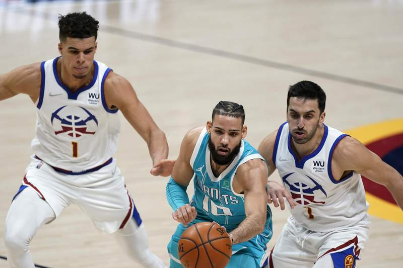 Charlotte Hornets forward Caleb Martin, center, passes the ball as he drives between Denver Nuggets forward Michael Porter Jr., left, and guard Facundo Campazzo during the second half of an NBA basketball game Wednesday, March 17, 2021, in Denver. (AP Photo/David Zalubowski)