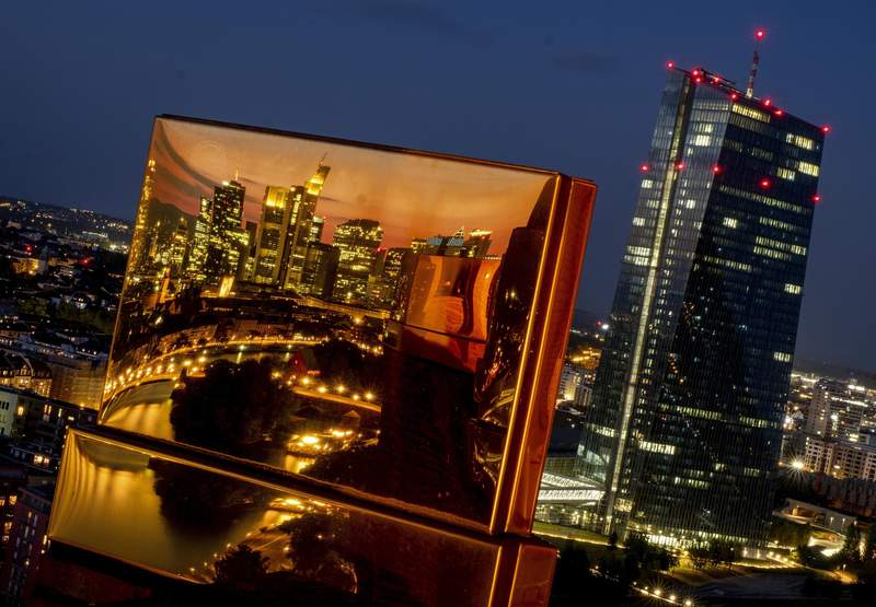 FILE - In this Sept.22, 2020 file photo red lights shine on the European Central Bank while the city's skyline is reflected in a golden architectural feature on top of a hotel in Frankfurt, Germany, Tuesday, Sept. 22, 2020. The European Union on Wednesday launched proceedings against Germany over a ruling by the top German court last year on a European Central Bank bond-buying program, which broke with a verdict from the EU's own top court. Brussels says that constitutes a serious precedent.(AP Photo/Michael Probst, file)
