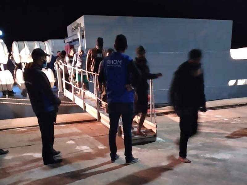 This photo provided by the International Organisation for Migration (IOM) Tunisia shows migrants disembarking in Tunisia, late Monday, May 17, 2021. Tunisian authorities say more than 50 migrants have drowned off the coast of the North African country, while 33 others were rescued by workers from an oil platform. (IOM Tunisia via AP)