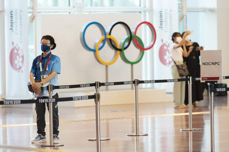 A Tokyo 2020 staff member stands by to help direct team members from other countries for the Tokyo 2020 Summer Olympic and Paralympic Games as they arrive at Haneda international airport in Tokyo on Sunday, July 18, 2021. (AP Photo/Hiro Komae)