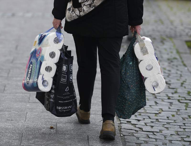A woman carries her shopping including bags of toilet paper, in downtown Frankfurt, Germany, Wednesday, March 18, 2020. Because of the spread of the coronavirus, bars, cinemas, theatres, museums, and many shops are now closed. For most people, the new coronavirus causes only mild or moderate symptoms. For some it can cause more severe illness. (Arne Dedert/dpa via AP)