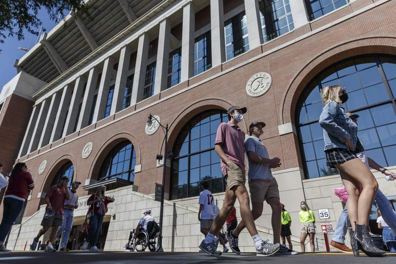 Fans meander along Paul W. Bryant Drive with Bryant-Denny Stadium's south facade as a backdrop Saturday, Oct. 3, 2020, in Tuscaloosa, Ala. Only 20,000 fans were allowed to attend the NCAA college football game between Alabama and Texas A&M, meaning many did not travel to the city, while others sought social opportunities at restaurants and bars. (AP Photo/Vasha Hunt)