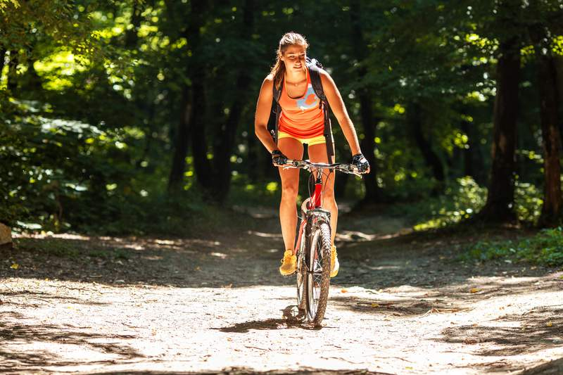 Female cyclist riding her mountain bike on country road.