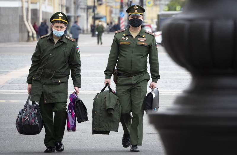Russian army officers wearing face masks to protect against coronavirus walk in St.Petersburg, Russia, Tuesday, May 19, 2020. Russia has continued to see a steady rise of new infections, and new hot spots have emerged across the vast country of 147-million people that ranks the second in the world behind the United States in the number of coronavirus cases. (AP Photo/Dmitri Lovetsky)