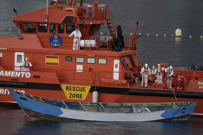 FILE  - In this Wednesday, April 28, 2021 file photo, a wooden boat is towed by a Spanish Maritime Rescue Service ship as they arrive at the port of Los Cristianos in the south of Tenerife, in the Canary Island, Spain. At least 29 Africans, including seven girls, died last week while trying to reach Spains Canary Islands by boat, a United Nations agency and Spanish non-profit assisting migrants in peril said Monday, Aug. 30, 2021. Spanish maritime rescue services on Friday rescued 27 migrants and recovered 4 bodies in the boat spotted by a fishing vessel south of the archipelago off northwest Africa. (AP Photo/Andres Gutierrez, File)